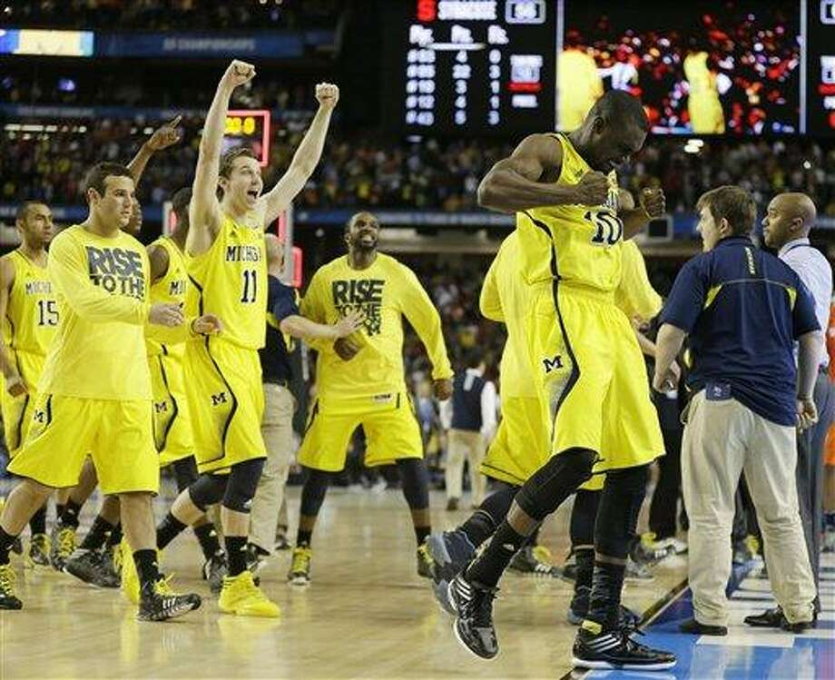Michigan players react after the second half of the NCAA Final Four tournament college basketball semifinal game against Syracuse, Saturday, April 6, 2013, in Atlanta. Michigan won 61-56. (AP Photo/Charlie Neibergall) Photo: ASSOCIATED PRESS / AP2013
