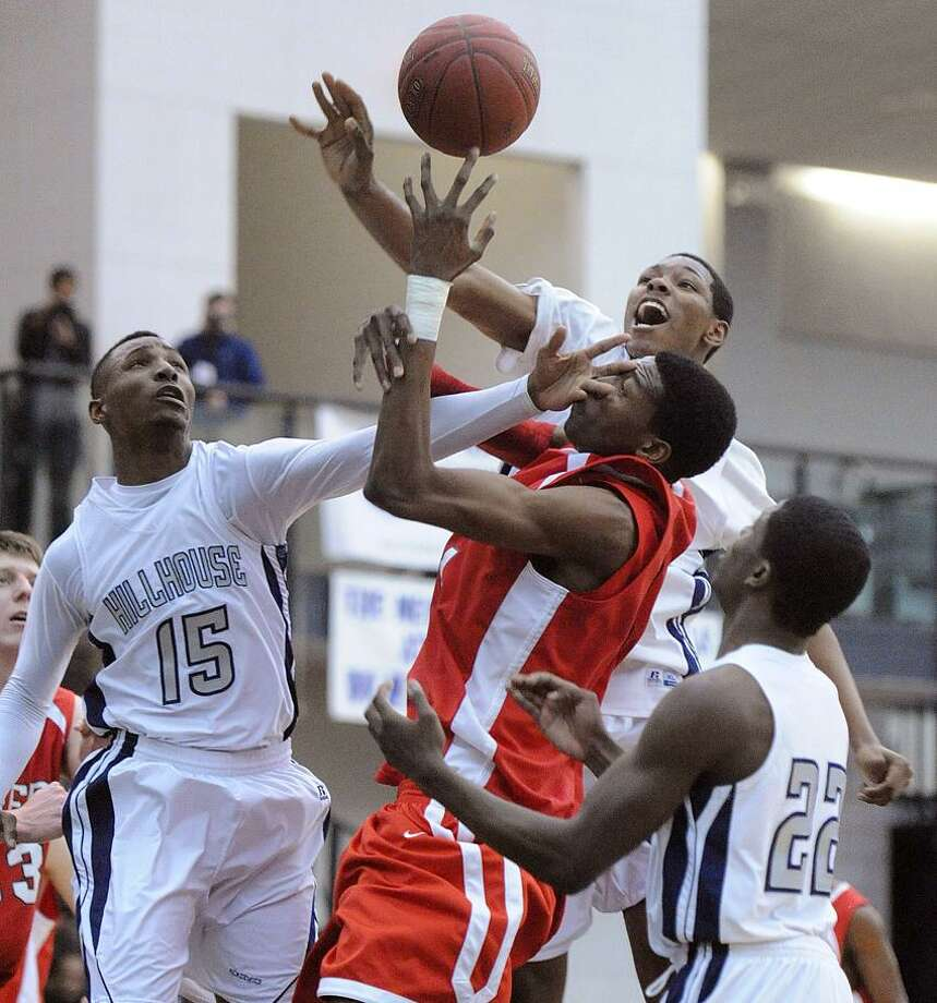 Fairfield Prep's 7 footer, Paschal Chukwu, gets no respect under the basket as Hillhouse's Quiaun Sturges, left, Chaise Daniels and Shane Christie defend during the first half of Prep's 57-52 win. Photo-Peter Casolino/Register.