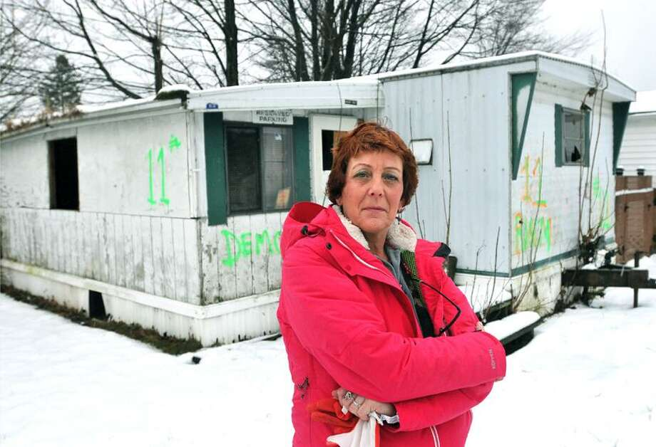 Branford-- Diane Lane, a resident in the Shoreline Mobile Trailer Park, stands in front of one of the 8 mobile homes that are vacant and overrun with feral cats according to Lane. Photo-Peter Casolino 1/16/13