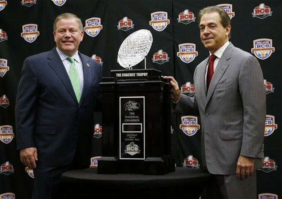 Alabama head coach Nick Saban and Notre Dame head coach Brian Kelly pose with The Coaches' Trophy during a news conference for the BCS National Championship college football game Sunday, Jan. 6, 2013, in Miami. (AP Photo/John Bazemore) Photo: AP / AP