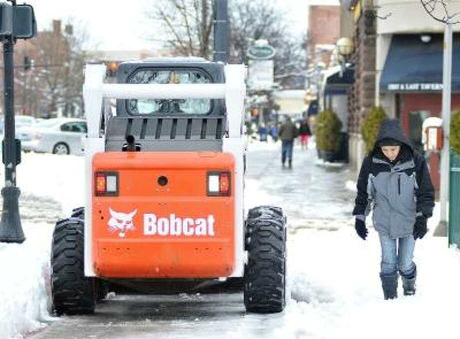 "Catherine Avalone/The Middletown Press  Plows and pedestrians shared the sidewalk Friday afternoon on Main Street in Middletown. Iris Plaza, of Middletown, at right said, ""Hopefully we get a good day soon"" as she trudged through the recent snowfall. / TheMiddletownPress"