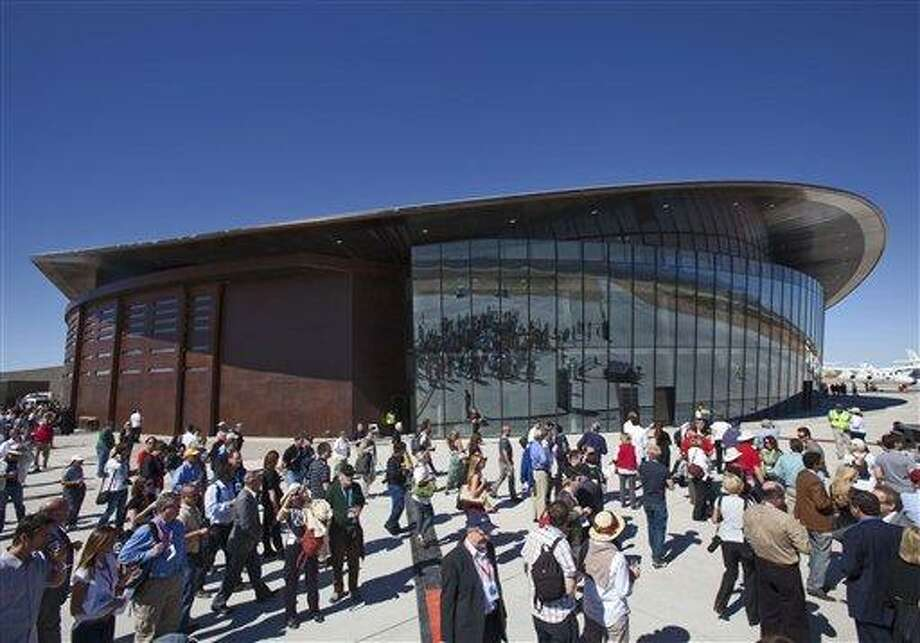 FILE - In this Oct. 17, 2011 file photo, guests stand outside the new Spaceport America hangar in Upham, N.M. Spaceport America officials are urging legislators to limit potential lawsuits from wealthy outer space tourists who take off from New Mexico, saying such a bill is crucial to the future of the project. (AP Photo/Matt York, File) Photo: AP / AP