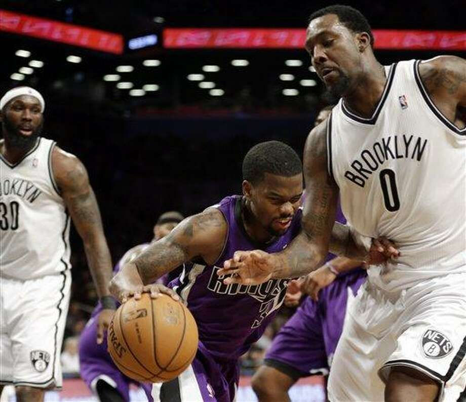 Sacramento Kings' Aaron Brooks (3) is defended by Brooklyn Nets' Andray Blatche (0) during the first half of an NBA basketball game Saturday, Jan. 5, 2013, in New York.  (AP Photo/Frank Franklin II) Photo: AP / AP