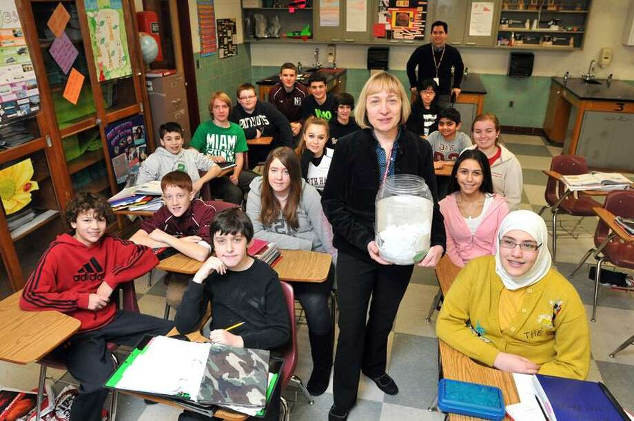 "North Haven-- North Haven Middle School science teacher Clara Laster, with her students are participating in ""26 Acts of Kindness"" at the school. She is holding a jug containing some of the notes describing each act that the students have done so far. The 26 acts of kindness represent the victims of the Sandy Hook shootings. Photo-Peter Casolino 1/28/13"