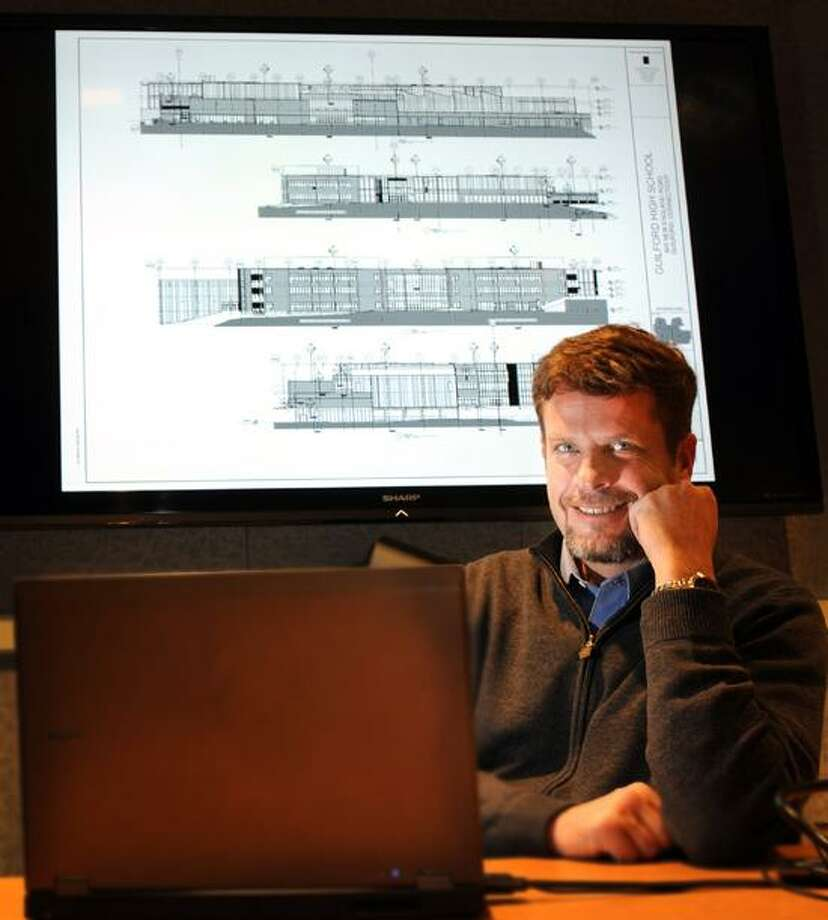 Scott Pinckney, Chairman of the Guilford High School building committee, sits next to a projection of a construction document progress set of the high school on a flat screen monitor Friday, January 05, 2013. The design plans show the East, North, West and south views of the proposed new Guilford H.S. Photo by Peter Hvizdak / New Haven Register and Michael Duffy / News-Times Photo: New Haven Register / ©Peter Hvizdak /  New Haven Register