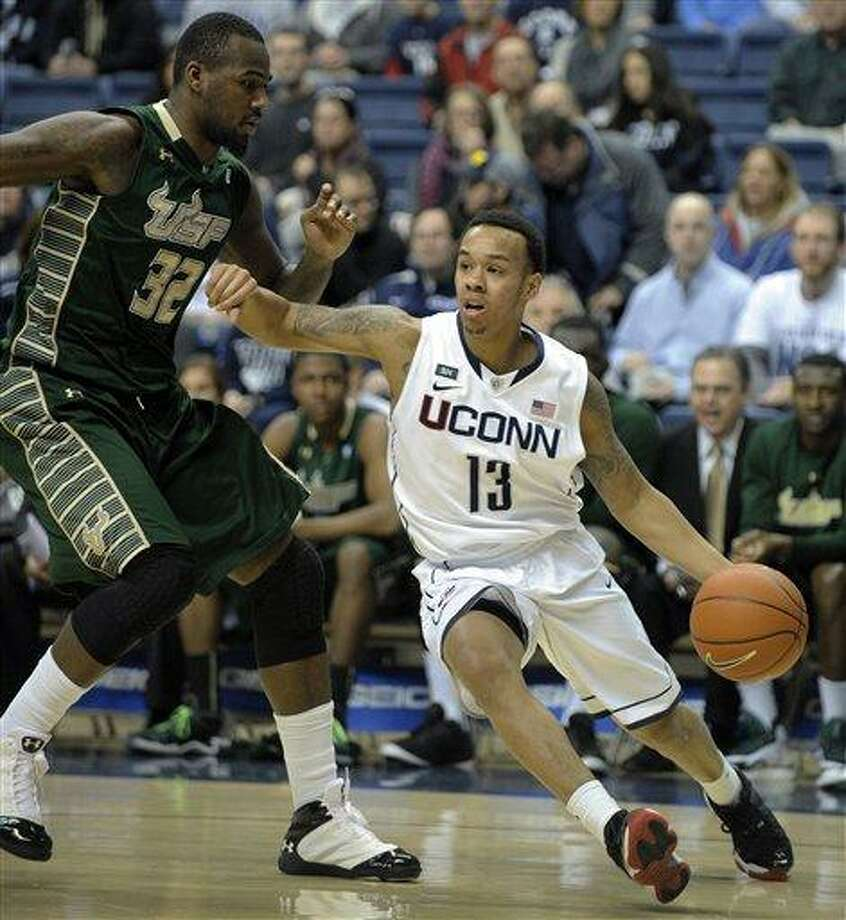 Connecticut's Shabazz Napier, right, drives past South Florida's Toarlyn Fitzpatrick during the first half of an NCAA college basketball game in Storrs, Conn., Sunday, Feb. 3, 2013. (AP Photo/Fred Beckham) Photo: AP / FR153656 AP