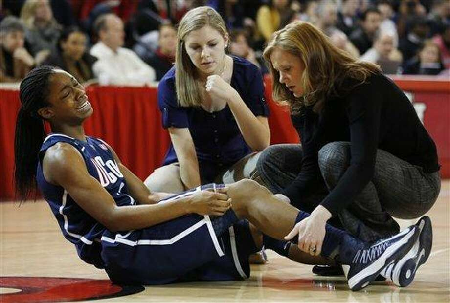 Connecticut guard Brianna Banks (13) winces in pain after an injury during the first half of a NCAA college basketball game against St. John's, Saturday, Feb. 2, 2013, at St. John's University in New York. (AP Photo/John Minchillo) Photo: AP / FR170537 AP