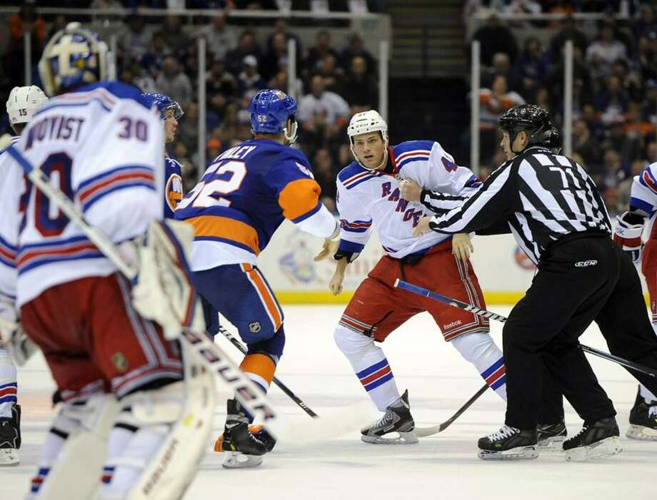 A referee breaks up a fight between New York Islanders' Joe Finley (52) and New York Rangers' Stu Bickel (41) in the second period of an NHL hockey game, Thursday, March 7, 2013, at Nassau Coliseum in Uniondale, N.Y. (AP Photo/Kathy Kmonicek) Photo: AP / FR170189 AP