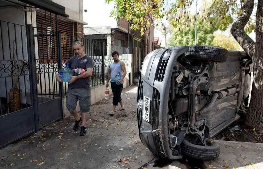 Men carry water past a car that flipped on its side during flooding in La Plata, in Argentina's Buenos Aires province, Thursday, April 4, 2013. Buenos Aires Gov. Daniel Scioli says 49 people died in this flooded capital of Argentinaís largest province as torrential rains swamped entire neighborhoods, washing away cars and flooding some houses to their rooftops. The overall death toll is now 55, and more than 20 people are missing. (AP Photo/Natacha Pisarenko) Photo: ASSOCIATED PRESS / AP2013