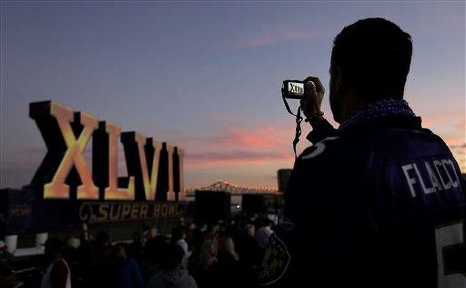 Greg Fox, from Baltimore, Md., photographs the Roman numerals for NFL Super Bowl XLVII as they they float on the Mississippi River Saturday, Feb. 2, 2013, in New Orleans. The city will host the football game between the San Francisco 49ers and Baltimore Ravens on Sunday. (AP Photo/Charlie Riedel) Photo: AP / AP