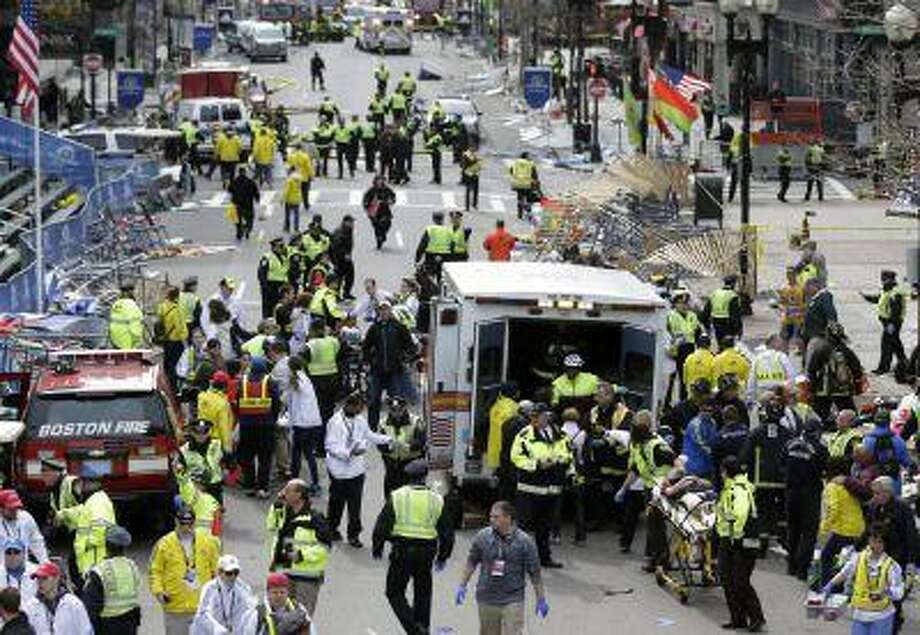 Medical workers aid injured people at the finish line of the 2013 Boston Marathon following an explosion in Boston, Monday, April 15, 2013. Photo: AP / 2013 A