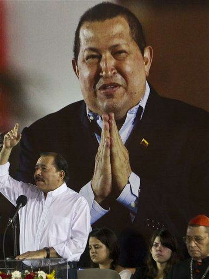 Nicaragua's President Daniel Ortega, centers, gestures as he delivers a speech in front of an image of Venezuela's President Hugo Chavez during a ceremony honoring Chavez in Managua, Nicaragua, Tuesday, March 5, 2013. Venezuela's Vice President Nicolas Maduro announced that Chavez died on Tuesday at age 58 after a nearly two-year bout with cancer.  Bottom right is the Archbishop of Managua Miguel Obando y Bravo.(AP Photo/Esteban Felix) Photo: AP / AP