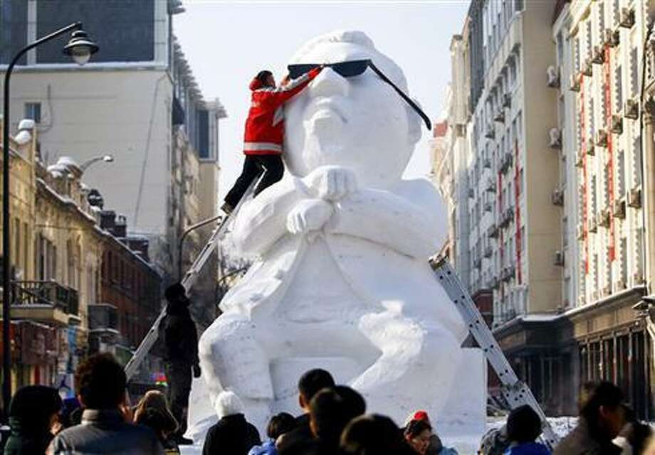 A worker puts sunglasses on the six-meter-tall snow sculpture of South Korean rapper PSY for the upcoming Ice Festival in Harbin in northeast China's Heilongjiang province Sunday, Dec. 16, 2012. The city is preparing for its annual ice festival where large blocks of ice are used to build a tourist attraction. (AP Photo) CHINA OUT Photo: AP / CHINATOPIX