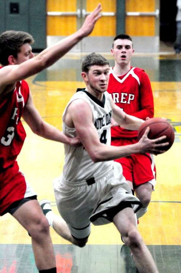 Joseph Bongiorni of Notre Dame of West Haven drives past Tim Butala, left, of Fairfield Prep Friday in Prep's 74-57 win. Photo by Arnold Gold/New Haven Register.