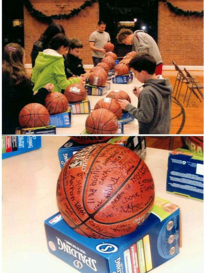Players sign the basketballs in North Haven for delivery to Newtown.