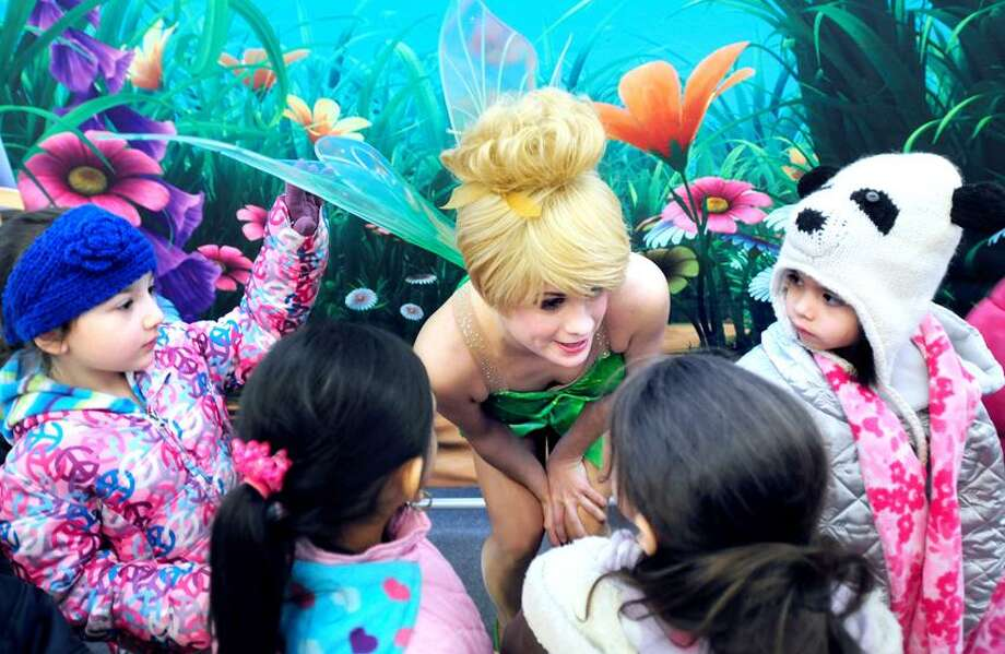 """Irving School kindergartener Dina Charachfi (left), 5, touches Tinkerbell's wing after a reading of Disney books by skaters from the """"Disney on Ice, Worlds of Fantasy"""" at the Derby Public Library in Derby on 1/3/2013.Photo by Arnold Gold/New Haven Register  AG0479A"""