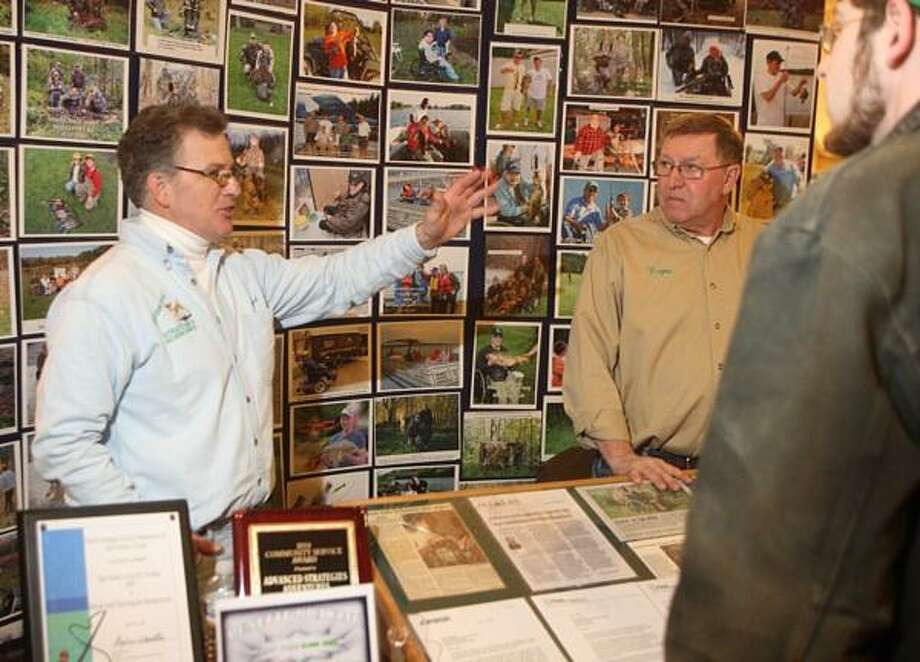 "Dispatch Staff Photo by JOHN HAEGER <a href=""http://twitter.com/oneidaphoto"">twitter.com/oneidaphoto</a> Lloyd Weigel of Advance Strategies Adventures  Inc  talks with show goers at his booth during the Sportsmen Show at the Kallet Civic Center in Oneida on Saturday, Feb. 2, 2013. Weigel was named Sportsmen of the Year"