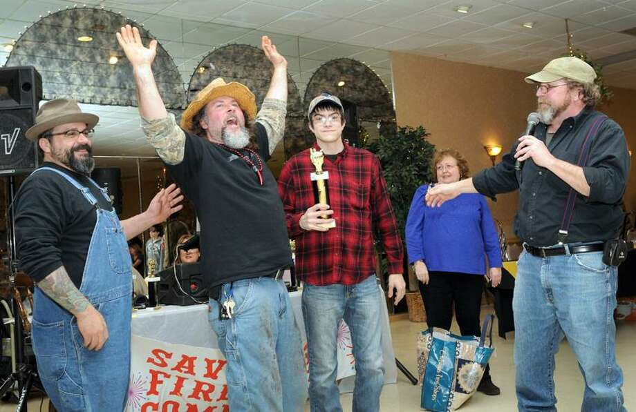 "Peter Hvizdak/Register photo: Hillbilly Chili's John Chiesa, left, Robert Saksa and Joey Chiesa, all of Shelton, celebrate their trophy win for the ""Best Display"" after the announcement by John Kelly of West Haven during the ninth annual Savin Rock Fireworks Chili Cook-Off  fundraiser Feb. 23 at the West Haven Italian American Club Westwoods Ballroom. The Hillbilly Chili's also won third place for best chili. Photo: New Haven Register / ©Peter Hvizdak /  New Haven Register"