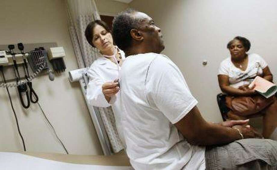 A man recieves a check up as his wife looks on at University of Chicago Medicine Primary Care Clinic in Chicago June 28, 2012. (REUTERS/Jim Young) / X90065
