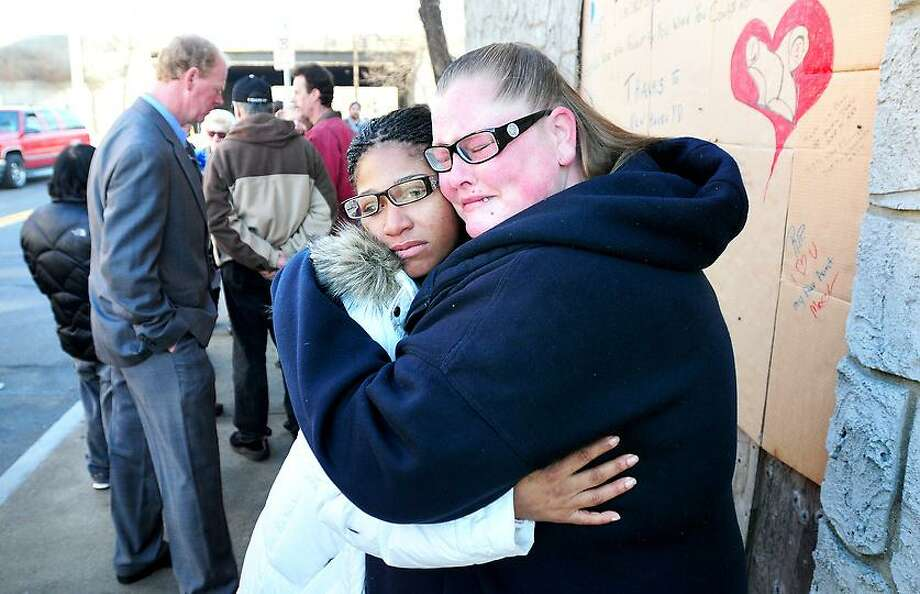 Monique Soules (center) hugs her cousin, Sherice Soules, during a memorial gathering on 1/1/2012 at 776-778 Grand Ave. in New Haven where Monique's mother, Louise Soules, and her boyfriend, Michael Mobley, were murdered in 2004.Photo by Arnold Gold/New Haven Register    AG0433F