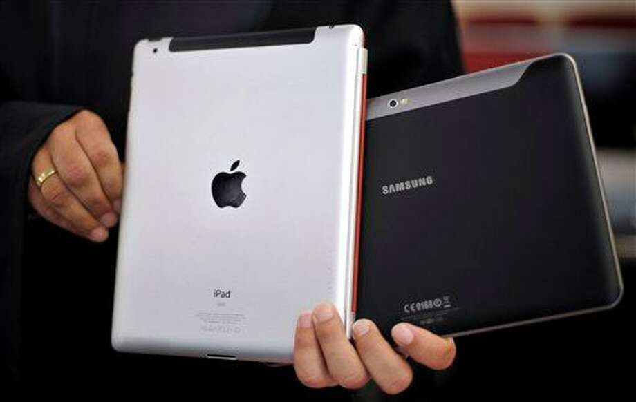 FILE - In this Aug. 25, 2011 file photo, an attorney holds an Apple iPad, left, and a Samsung Galaxy Tab 10.1 at the regional court in Duesseldorf, Germany. A federal judge on Friday, March 1, 2013 slashed nearly half of the $1 billion damage award a jury ordered Samsung Electronics to pay Apple Inc. after a high-profile trial over the rights to the design and technology running some of the world's most popular smartphones and tablet computers. (AP Photo/dapd, Sascha Schuermann, File) Photo: AP / dapd