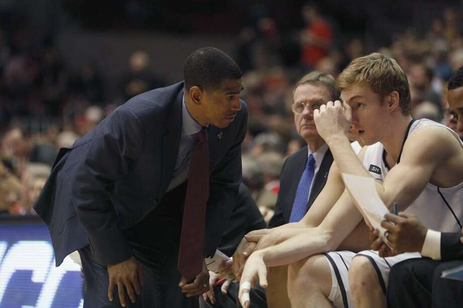 UConn coach Kevin Ollie, left, cannot look for help from forward Niels Giffey, right, for the  last two games of the season as Giffey has a dislocation fracture of his right index finger. Photo: AP / FR51830 AP