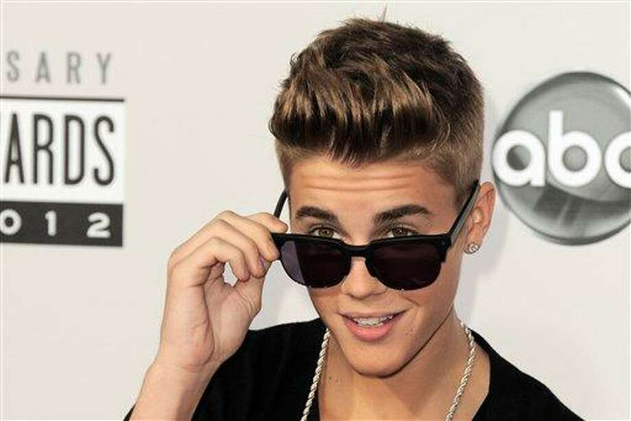 Justin Bieber arrives at the 40th Anniversary American Music Awards in Los Angeles. Police say a paparazzo was hit by a car and killed after taking photos of Justin Bieber's white Ferrari on a Los Angeles street Tuesday evening. Los Angeles police Officer James Stoughton says the photographer, who was not identified, died at a hospital shortly after the crash Tuesday evening. Stoughton says Bieber was not in the Ferrari at the time. Photo by Jordan Strauss/Invision/AP Photo: Jordan Strauss/Invision/AP / Invision