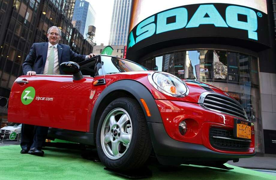 "FILE - In this April 14, 2011 file photo provided by <a href=""http://Zipcar.com"">Zipcar.com</a>, Zipcar Chairman and CEO Scott Griffith stands with a Zipcar Mini-Cooper before the opening bell at the NASDAQ Market Site in New York. Avis is buying Zipcar for $491.2 million, expanding its offerings from traditional car rentals to car sharing services. The boards of both companies unanimously approved the buyout. (AP Photo/Zipcar.com, Craig Ruttle, File) Photo: AP / A2011"