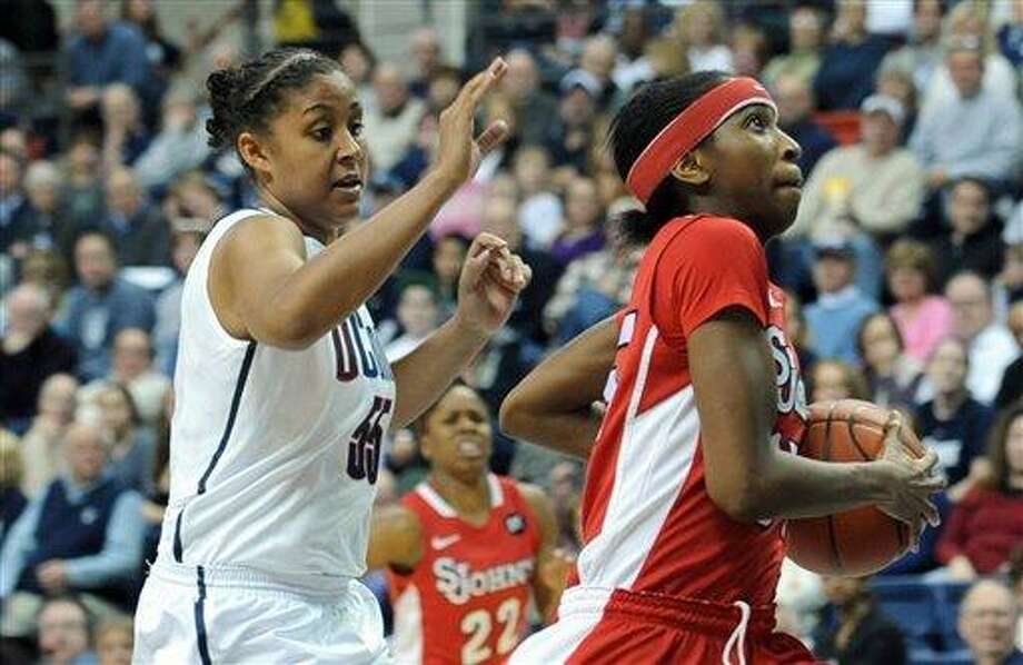 St. John's Shenneika Smith, right, runs for the basket while pursued by Connecticut's Kaleena Mosqueda-Lewis in the second half of an NCAA women's college basketball game at Storrs, Conn., Saturday, Feb. 18, 2012. St. John's defeated Connecticut 57-56. (AP Photo/Bob Child) Photo: ASSOCIATED PRESS / AP2012