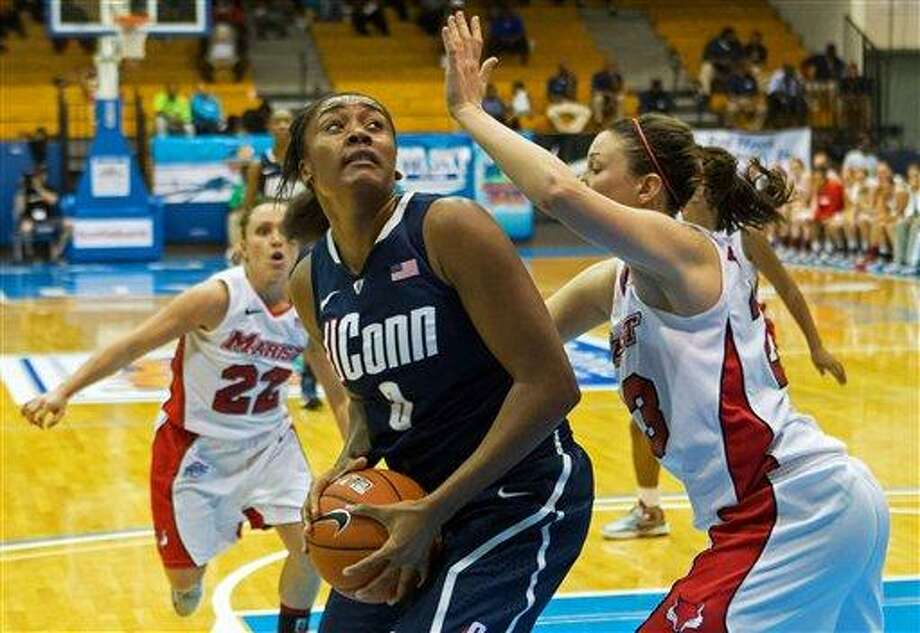 Connecticut's forward Morgan Tuck, left center, looks to shoot over Marist's guard Elizabeth Beynnon during the second half of an NCAA women's college basketball game in St. Thomas, U.S. Virgin Islands, Friday, Nov. 23, 2012. Connecticut won 81-39. (AP Photo/Thomas Layer) Photo: ASSOCIATED PRESS / AP2012