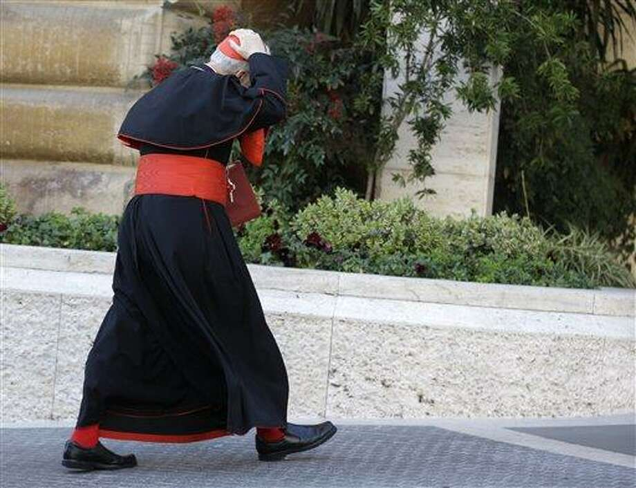 An unidentified cardinal holds his skull cap to prevent it from blowing away in the wind as he arrives for a meeting, at the Vatican, Monday, March 4, 2013. Cardinals from around the world have gathered inside the Vatican for their first round of meetings before the conclave to elect the next pope, amid scandals inside and out of the Vatican and the continued reverberations of Benedict XVI's decision to retire. (AP Photo/Andrew Medichini) Photo: AP / AP