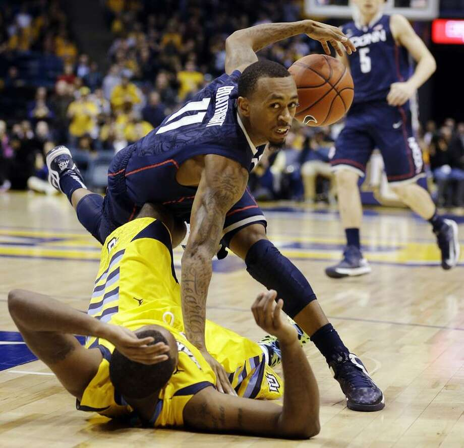 Connecticut's Ryan Boatright, top, tumbles over Marquette's Davante Gardner in overtime of an NCAA college basketball game, Tuesday, Jan. 1, 2013, in Milwaukee. Marquette won 82-76 in overtime. (AP Photo/Jeffrey Phelps) Photo: AP / AP2013
