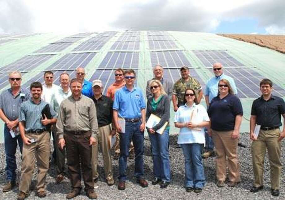 Members of the Central New York Branch of the American Public Works Association stand in front of the Madison County Landfill solar array.  The group awarded the County the Environmental Project of the Year Award for their solar cover.