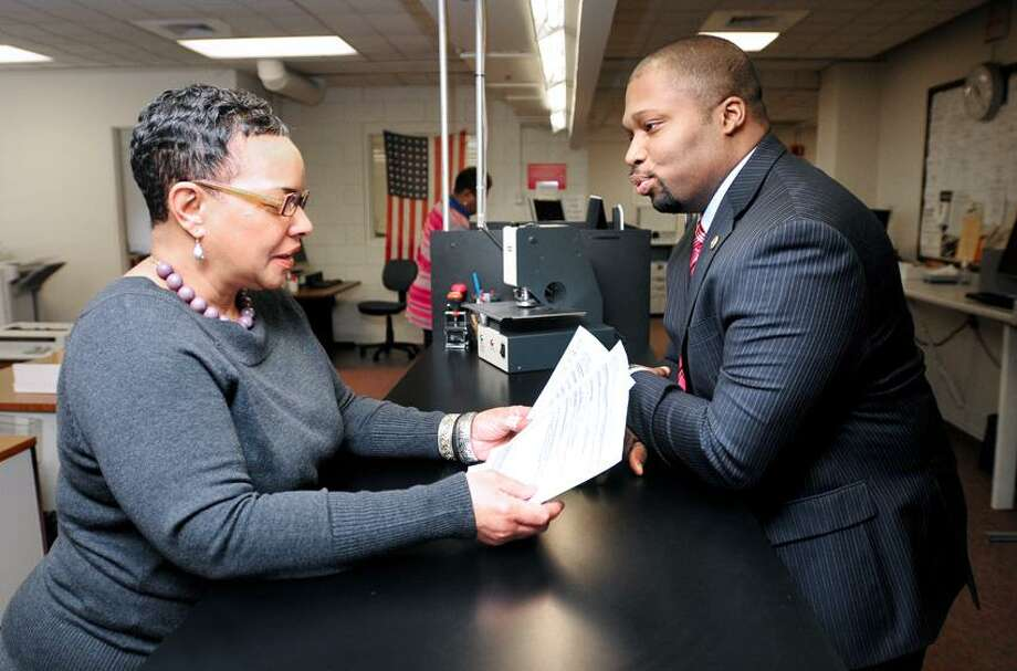Deputy City Clerk Sally Brown (left) looks over the paperwork State Rep. Gary Holder-Winfield (right) filed to run for mayor at the City Clerk's Office at the Hall of Records in New Haven on 2/1/2013.Photo by Arnold Gold/New Haven Register   AG0482D