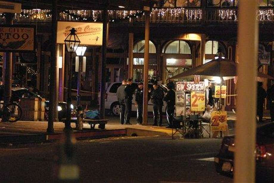 In this image provided by Robert Petersen police inspect the scene of a shooting outside the Sports Corner Cafe in Sacramento Calif. Monday Dec. 31, 2012. Police say two people died and three others were injured in a New Year's Eve shooting after a fight in a restaurant in the Old Sacramento area. After the shooting, police decided to cancel the area's midnight fireworks show, which were part of the New Year's Eve celebration. (AP Photo/Robert Petersen) Photo: AP / Robert Petersen
