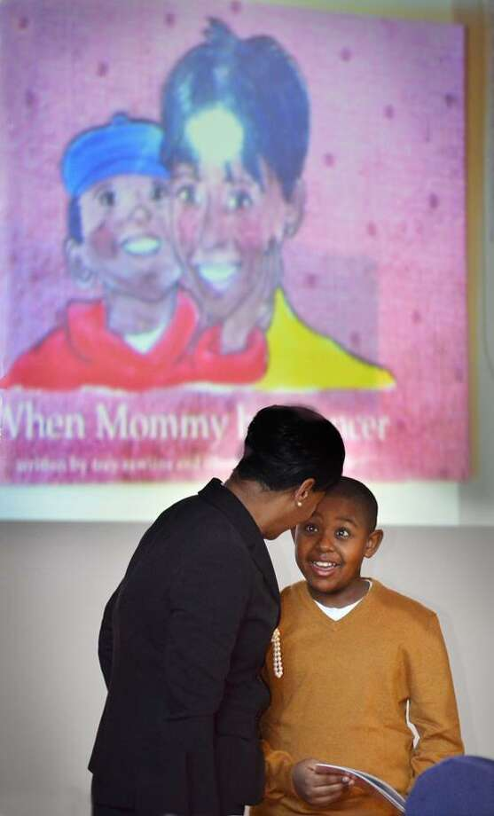 NEW HAVEN-James Rawlins reacts to praise from his mother, Veronica Marion Rawlins,after they read the book that they wrote together to Edgewood School students. as they read the pagres were projected on the screen behind them.   Melanie Stengel/Register