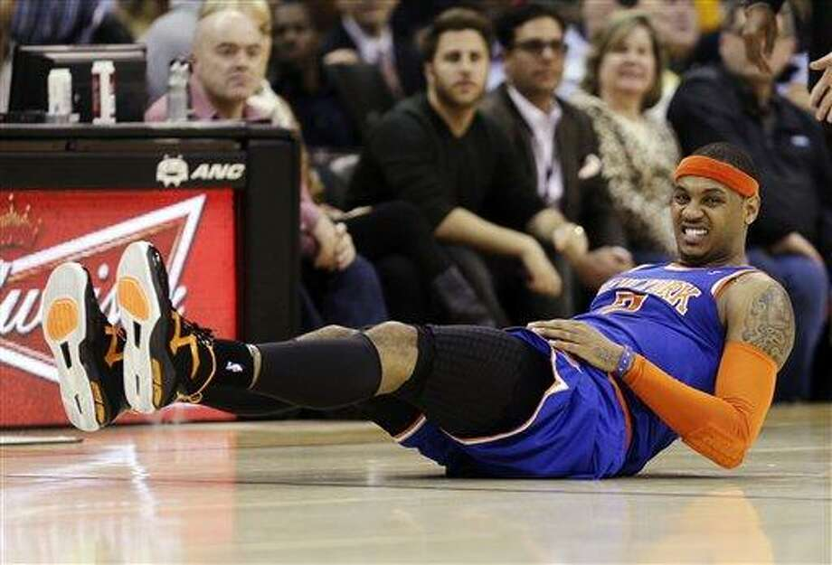 New York Knicks' Carmelo Anthony grimaces after falling in the second quarter of an NBA basketball game against the Cleveland Cavaliers, Monday, March 4, 2013, in Cleveland. (AP Photo/Tony Dejak) Photo: AP / AP