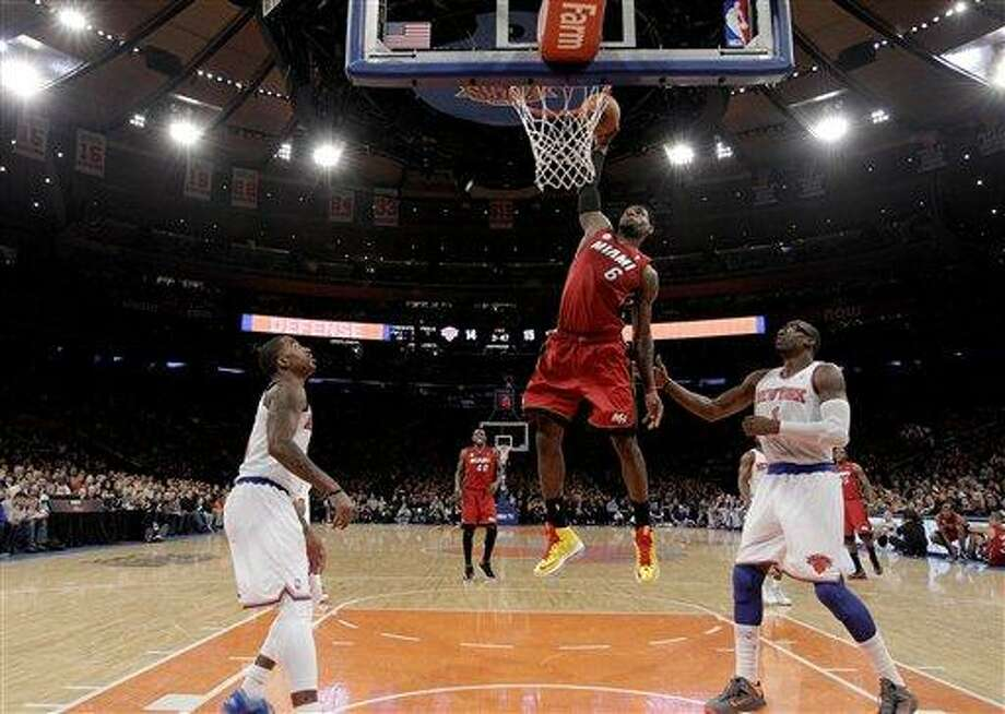 Miami Heat forward LeBron James (6) dunks in front of New York Knicks guard J.R. Smith, left, and forward Amare Stoudemire (1) during the second half of their NBA basketball game at Madison Square Garden in New York, Sunday, March 3, 2013. The Heat won 99-93. (AP Photo/Kathy Willens) Photo: AP / AP