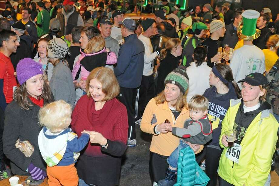 """From left to right, family members Lisa and Jan Stoffer of Wisconsin babysit Westley  (CQ) Rogers of New Haven and Jamie Beckman of Higganum, Conn. holds her son Hudson Beckman, 2,  as friend Kathy Hassen-Stack of North Branford watches the band on stage at The Diaper Bank 5K Road Race post race party at Toad's Place in New Haven Sunday, March 3, 2013. The race was fundraiser and diaper collection point for the The Diaper Bank which """"centralizes the fundraising and distribution of free diapers to poor families through existing service providers, including local food pantries, soup kitchens, daycare centers, social service agencies and shelters. Through its extensive Diaper Distribution Network (DDN) of 66 agencies, TDB provides over 200,000 free diapers monthly to poor and low-income families in New Haven, Bridgeport, Hartford, and Middlesex County,"""" according to The Diaper Bank website.Sunday, March 3, 2013 Photo by Peter Hvizdak / New Haven Register Photo: New Haven Register / ©Peter Hvizdak /  New Haven Register"""
