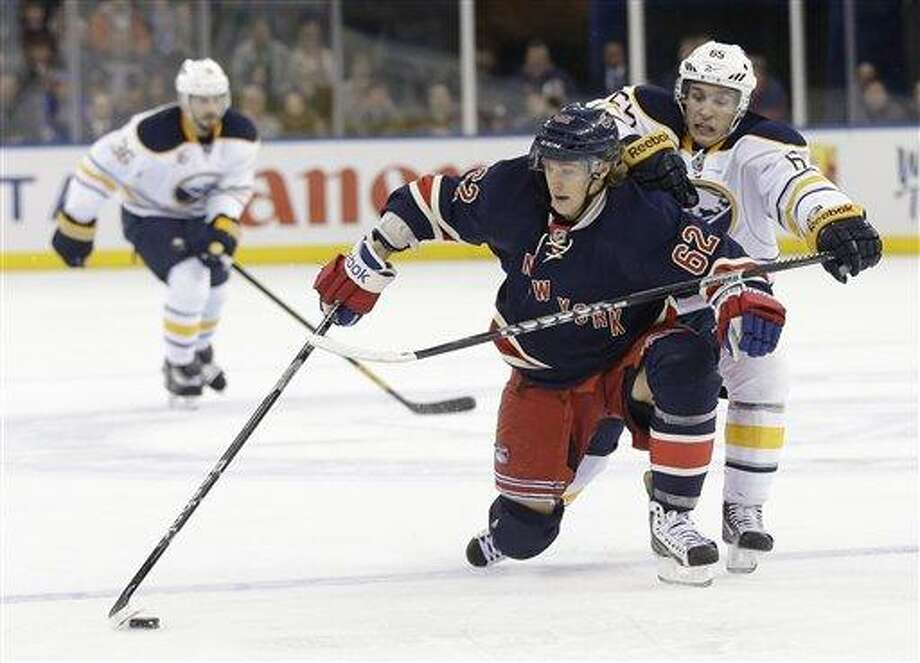 New York Rangers' Carl Hagelin, center, tries to keep the puck from Buffalo Sabres' Brian Flynn, right, during the second period of the NHL hockey game in New York, Sunday, March 3, 2013.  (AP Photo/Seth Wenig) Photo: AP / AP