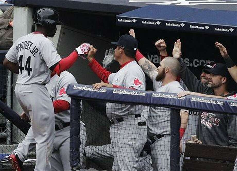 Boston Red Sox's Jackie Bradley, Jr. is congratulated by teammates as he returns to the dugout after collecting an RBI on a fielder's choice in the seventh inning of a baseball game against the New York Yankees at Yankee Stadium, Monday, April 1, 2013 in New York. (AP Photo/Mark Lennihan) Photo: AP / AP