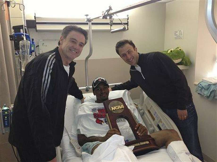In this photo released by the University of Louisville, injured Louisville guard Kevin Ware lies in a hospital bed holding the NCAA Regional Championship trophy flanked by coach Rick Pitino, left, and former Louisville assistant coach Richard Pitino, Monday, April 1, 2013, in Louisville, Ky. Ware broke his leg in the first half of Sunday's Midwest Regional final when he landed awkwardly after trying to contest a 3-point shot, breaking his leg in two places. He was taken off the court on a stretcher as his stunned teammates openly wept. His teammates went on to defeat Duke 85-63 to reach their second straight Final Four. (AP Photo/University of Louisville, Kenny Klein) Photo: ASSOCIATED PRESS / AP2013