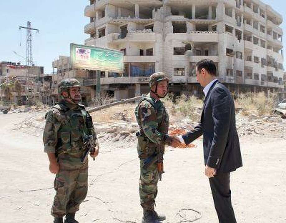 This image posted on the official Facebook page of the Syrian Presidency on Thursday, Aug. 1, 2013 purports to show Syrian President Bashar Assad shaking hands with a soldier during Syrian Arab Army day in Darya, Syria. Photo: ASSOCIATED PRESS / THE ASSOCIATED PRESS2013