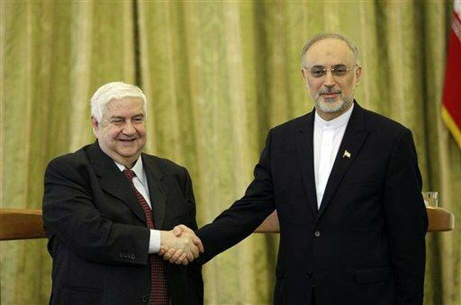Syrian Foreign Minister Walid al-Moallem, left, and his Iranian counterpart Ali Akbar Salehi, shake hands, at the conclusion of their press conference, in Tehran, Iran, Saturday, March 2, 2013. The Syrian and Iranian foreign ministers on Saturday accused the United States of double standards over the Obama administration's decision to provide aid to rebels fighting to topple President Bashar Assad, saying this will only prolong the conflict. (AP Photo/Vahid Salemi) Photo: AP / AP