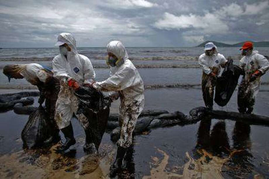 Thai soldiers wearing biohazard suits take part as cleaning operations continue at Ao Prao Beach on Koh Samet, Rayong July 31, 2013. Photo: REUTERS / X02943