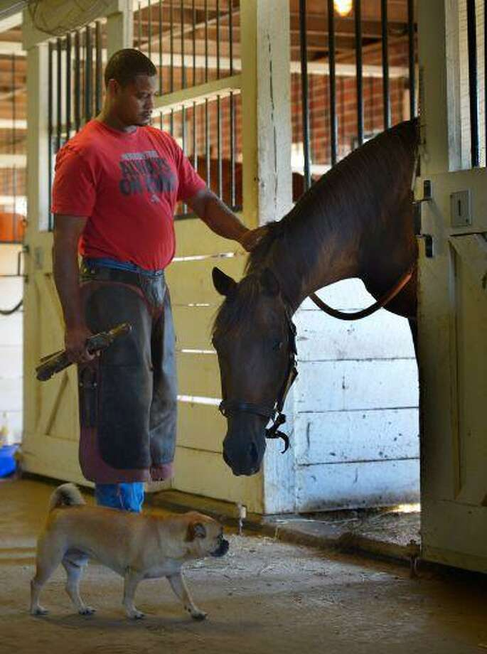 Former Virginia state inmate Tamio Holmes, a farrier, a skill he learned in prison, poses with Covert Action, grandson of Secretariat, in a stall at the James River Correctional Center in Crozier, Va., earlier this month. Photo: The Washington Post / The Washington Post