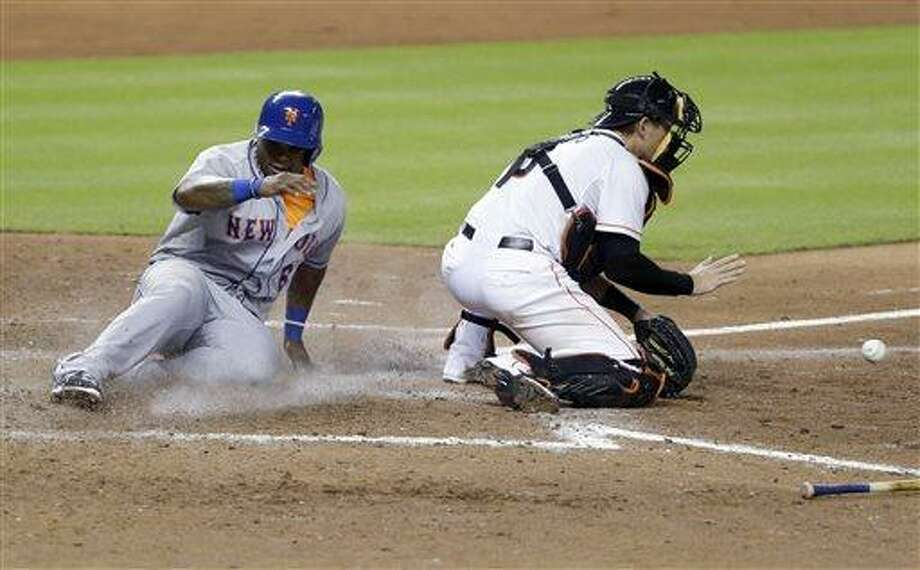 New York Mets' Marlon Byrd (6) scores behind Miami Marlins catcher Jeff Mathis during the 10th inning of a baseball game, Tuesday, July 30, 2013, in Miami. David Wright also scored on the play and the Mets defeated the Marlins 4-2 in 10 innings. (AP Photo/Wilfredo Lee) Photo: AP / AP