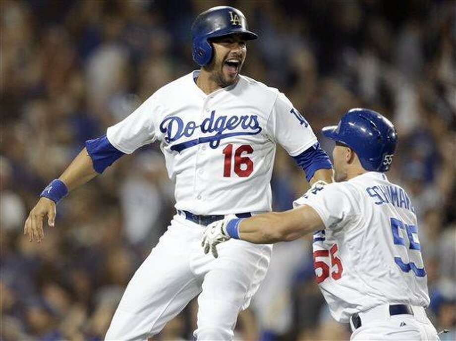 Los Angeles Dodgers' Andre Ethier, left, celebrates with Skip Schumaker after scoring the winning run on a hit by Mark Ellis against the New York Yankees during the ninth inning of a baseball game in Los Angeles, Tuesday, July 30, 2013. (AP Photo/Chris Carlson) Photo: AP / AP