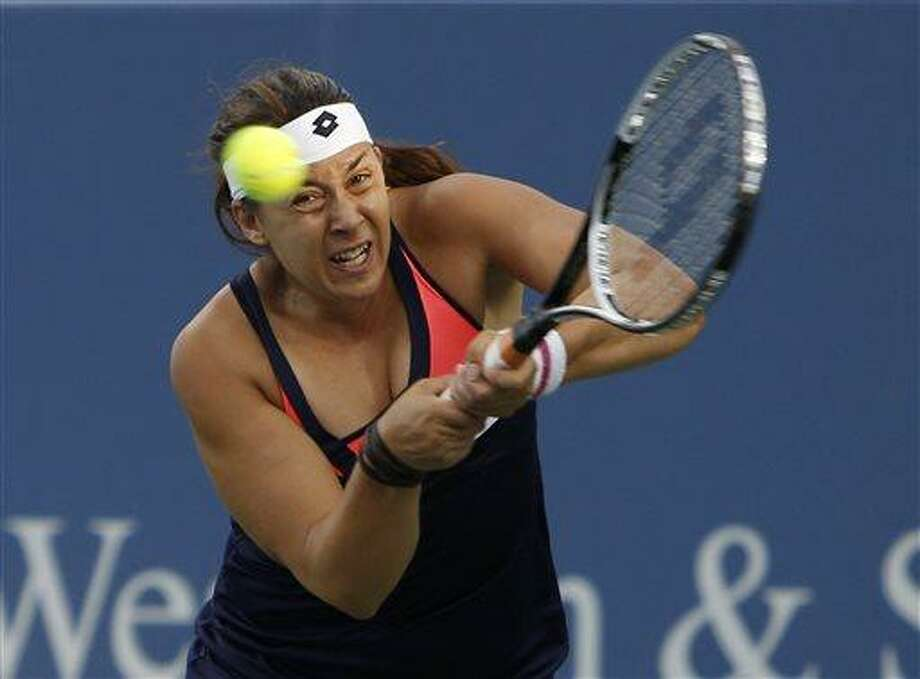 Marion Bartoli, from France, returns against Simona Halep, from Romania, during a match at the Western & Southern Open tennis tournament, Wednesday, Aug. 14, 2013, in Mason, Ohio. (AP Photo/David Kohl) Photo: AP / FR51830 AP