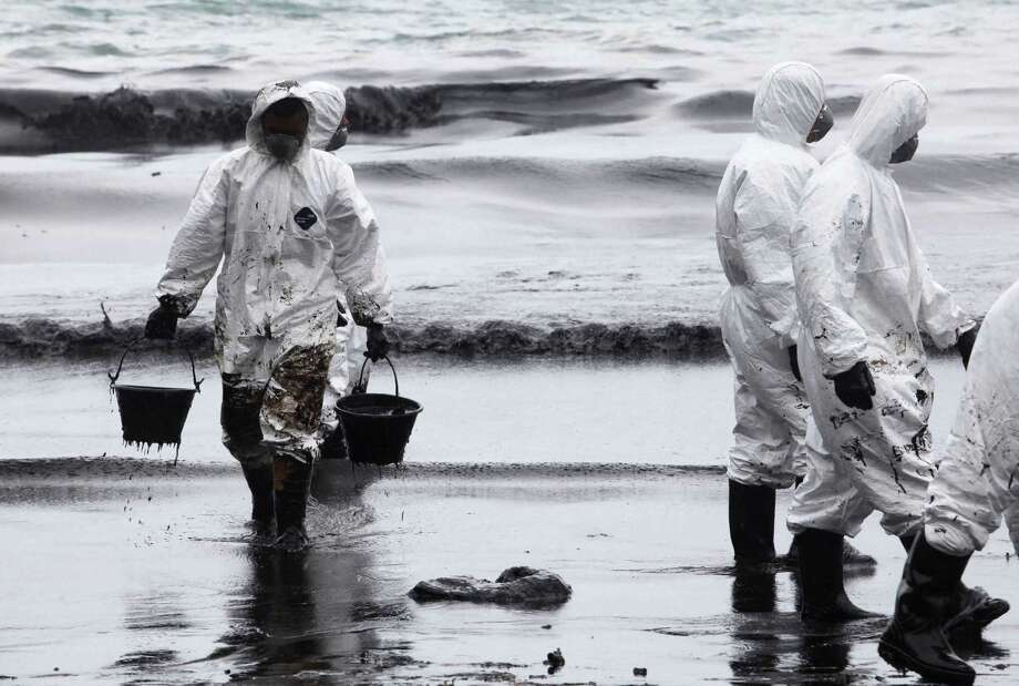 Workers use buckets to remove crude oil during a clean up operation on the beach of Prao Bay on Samet Island in Rayong province eastern Thailand Tuesday, July 30, 2013. About 50,000 liters (13,200 gallons) of crude oil that leaked from a pipeline operated by PTT Global Chemical Plc, has reached the popular tourist island in Thailand's eastern sea despite continuous attempts to clean it up.  (AP Photo) Photo: ASSOCIATED PRESS / AP2013